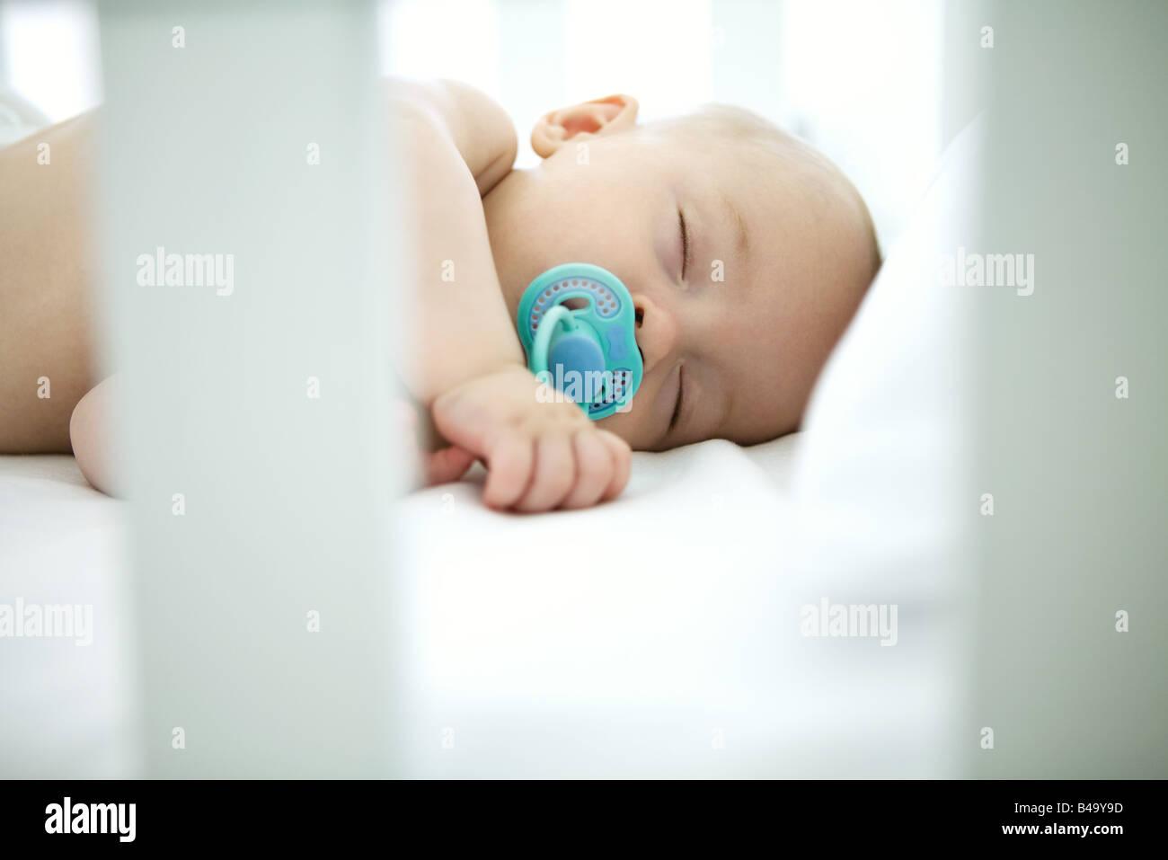 Baby schläft in Krippe, Schnuller im Mund Stockbild