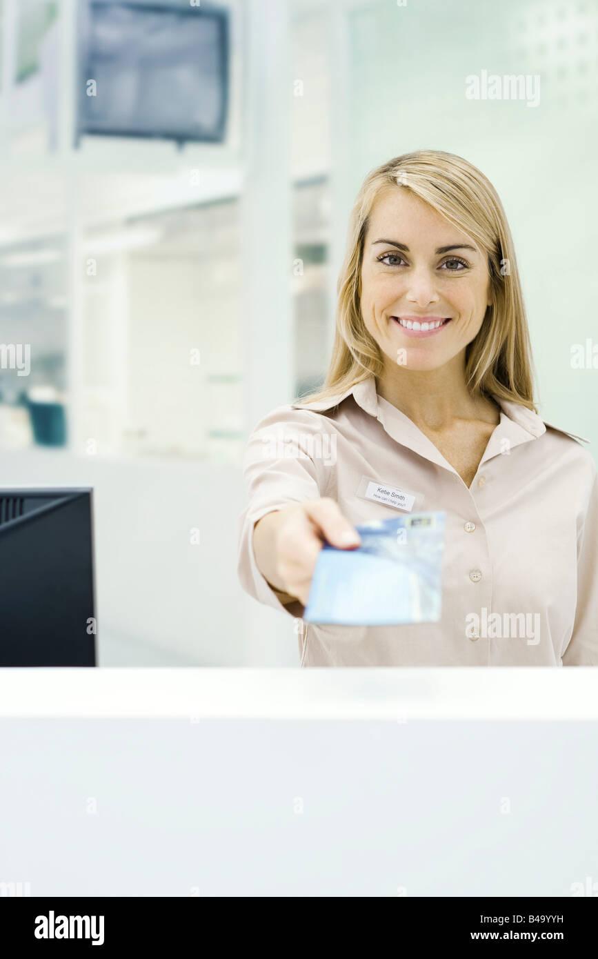 Reisebüro Ticket, hält lächelnd in die Kamera, persönliche Perspektive Stockbild