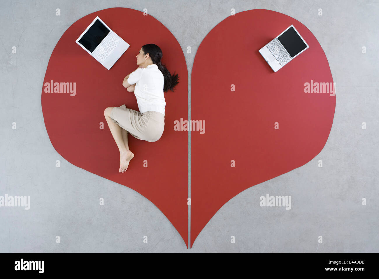 Frau auf dem Boden liegend mit Laptop auf großen Liebeskummer, verlassen Laptop hinter ihr Stockfoto