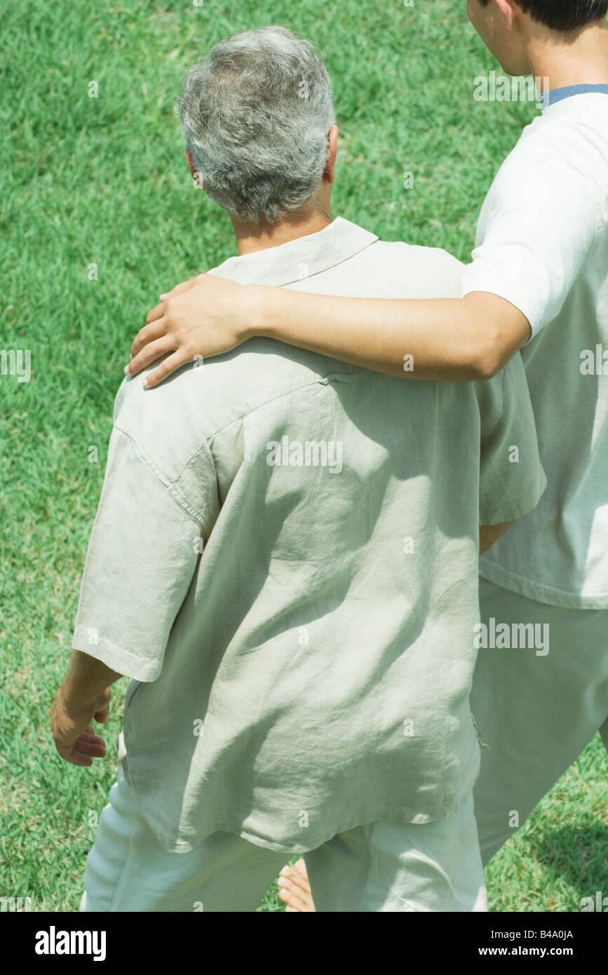 Junger Mann mit seinem Arm über die Schulter von einem älteren Mann zusammen spazieren über den Rasen Stockbild