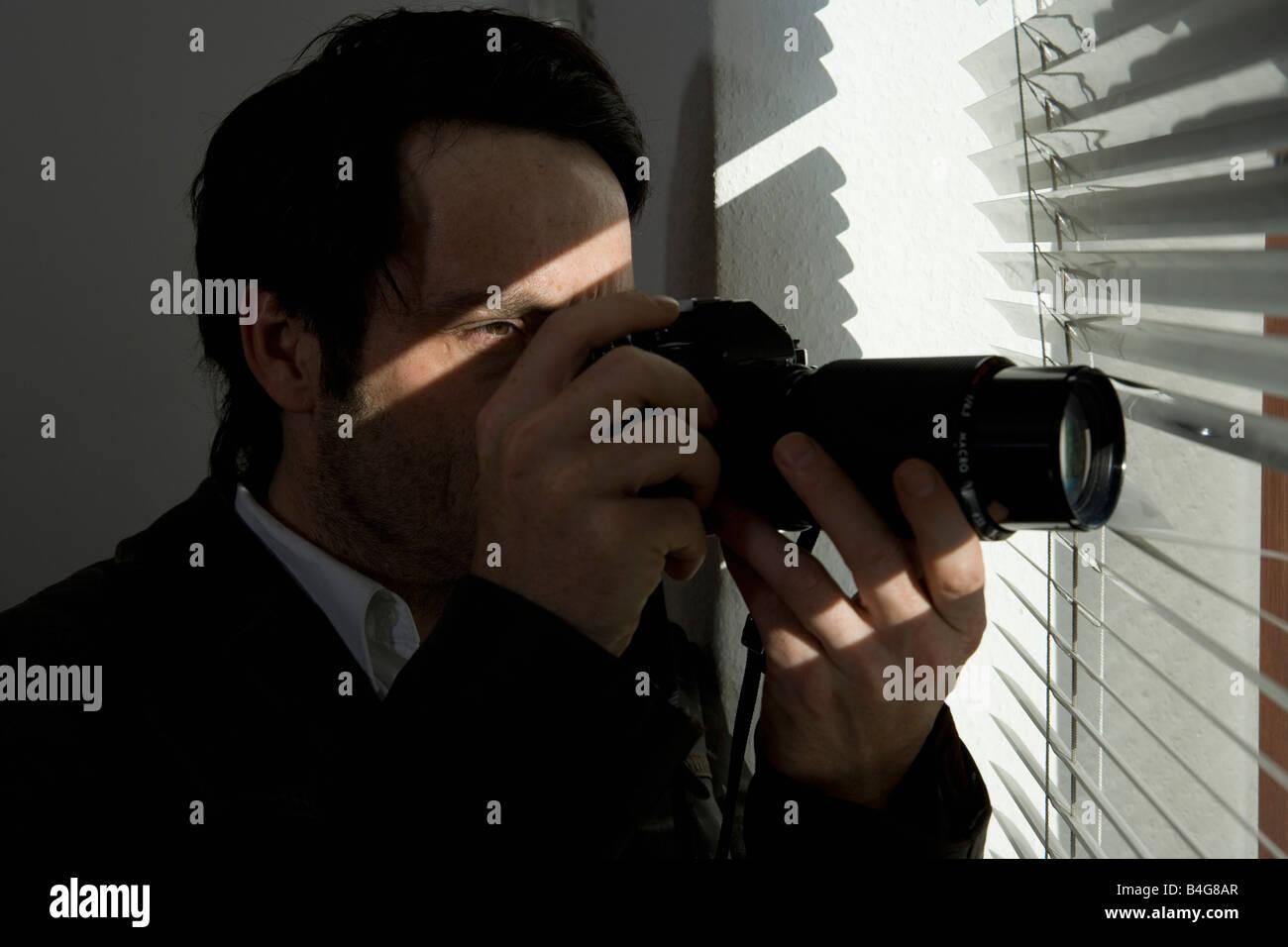 Ein Mann auf der Suche durch Jalousien mit einer Kamera Stockbild