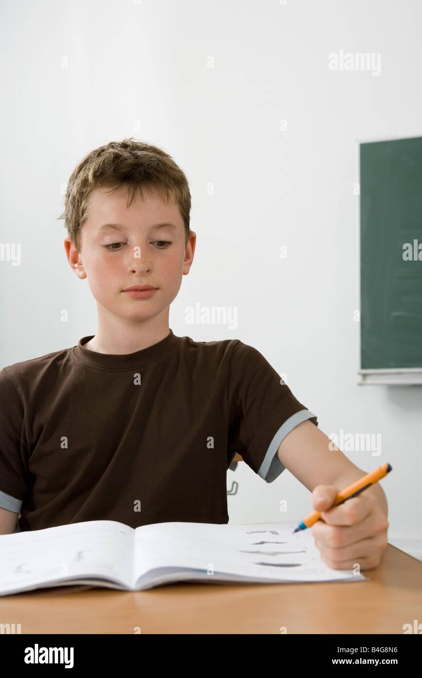 Ein Pre-heranwachsenden Jungen studieren in einem Klassenzimmer Stockbild