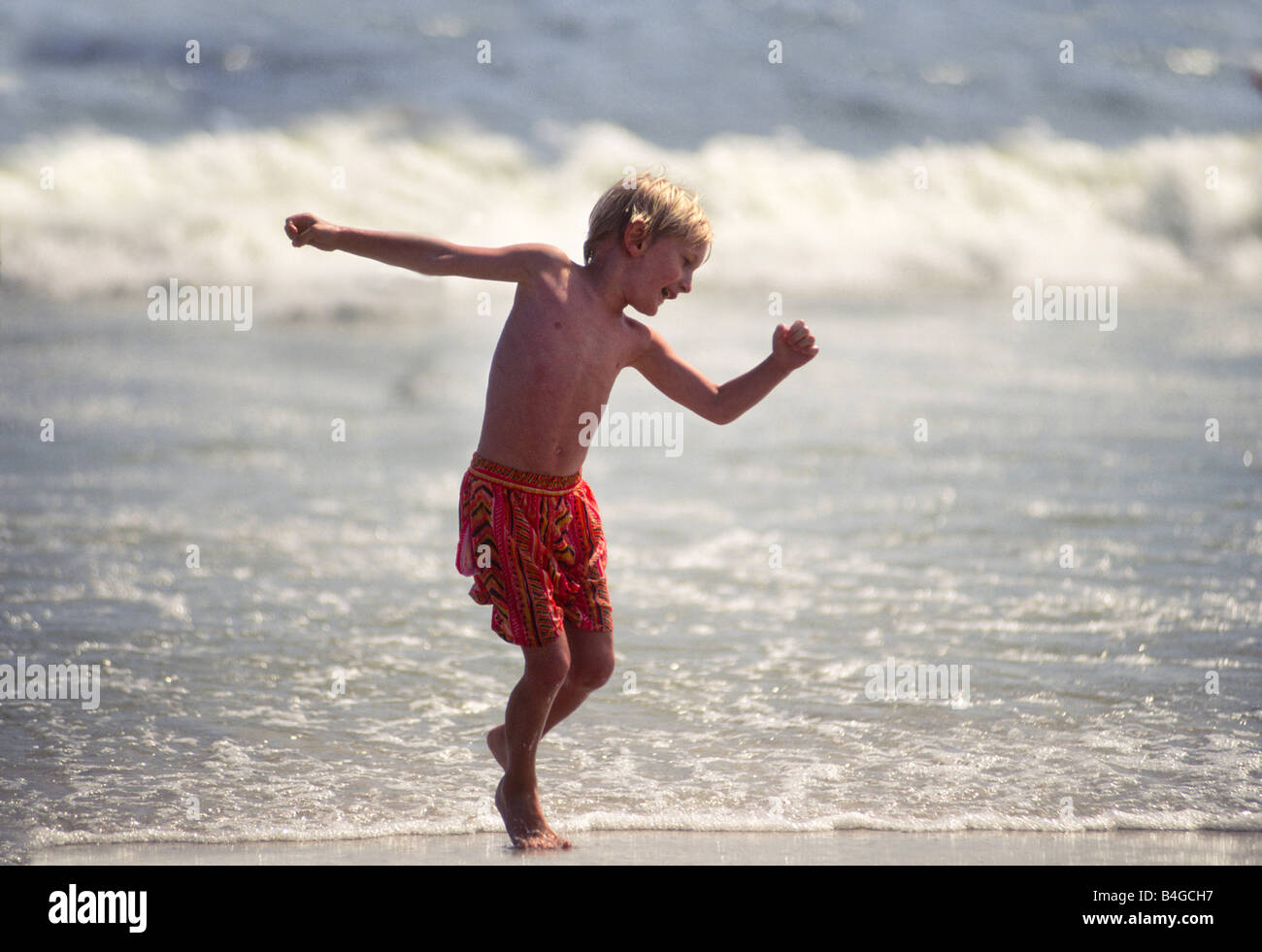 kleiner Junge tanzt um ankommendes Wasser am Ufer zu vermeiden Stockbild