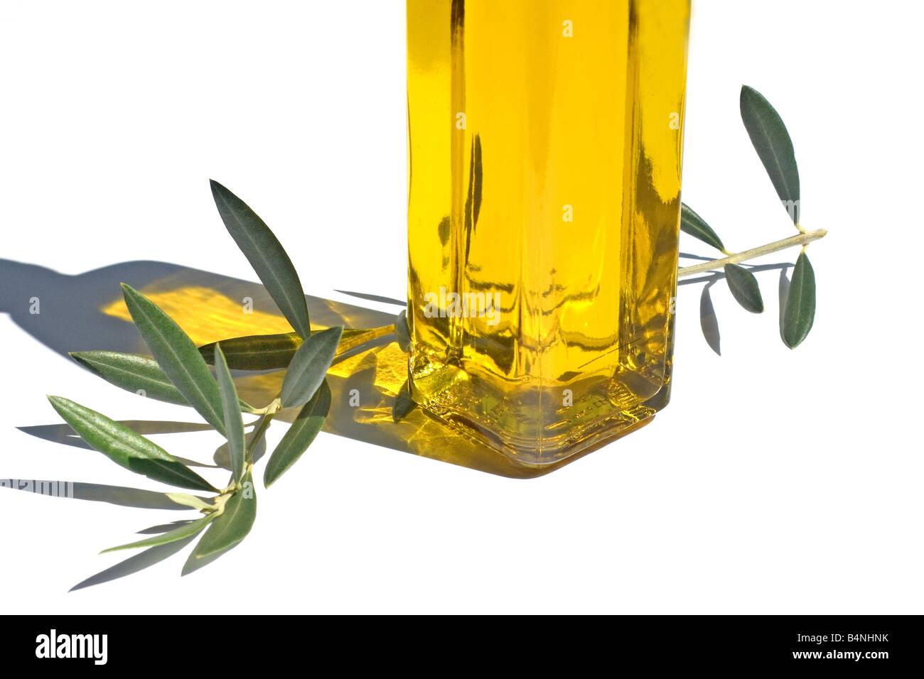 Olivenöl und Blätter auf weißem Hintergrund Stockbild