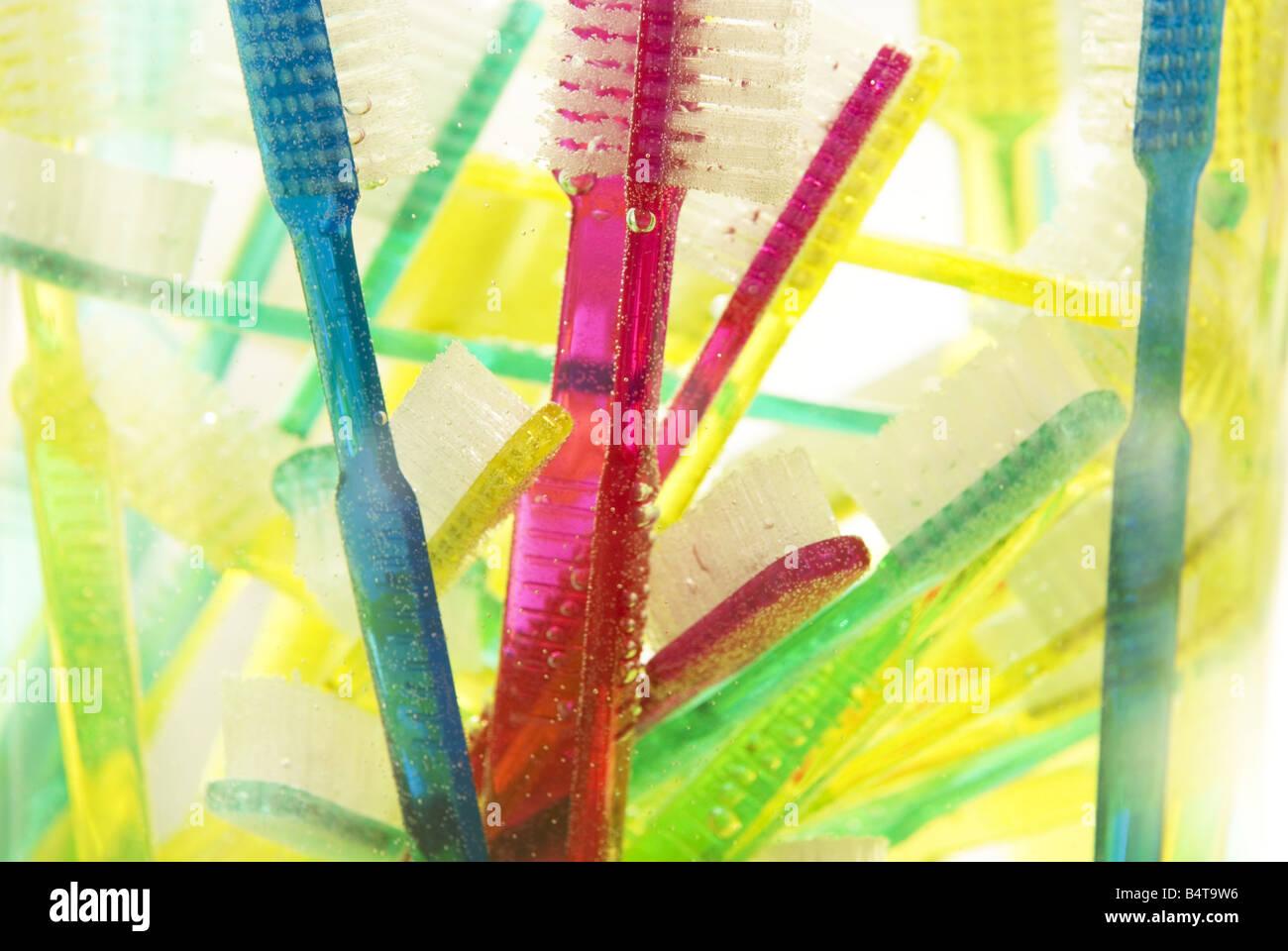 Nahaufnahme von untergetaucht und schwimmenden bunten Zahnbürsten in Glasvase Stockbild