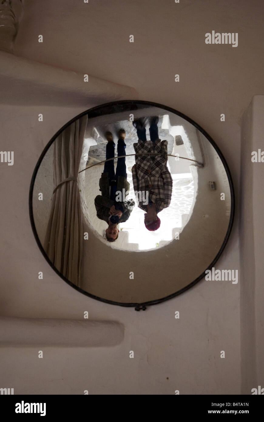 paar in der Tür stehend reflektiert kopfüber in konvexe Spiegel Stockbild