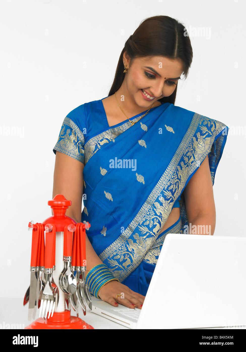 eine lächelnde asiatische Frau indischer Herkunft mit ihrem laptop Stockfoto