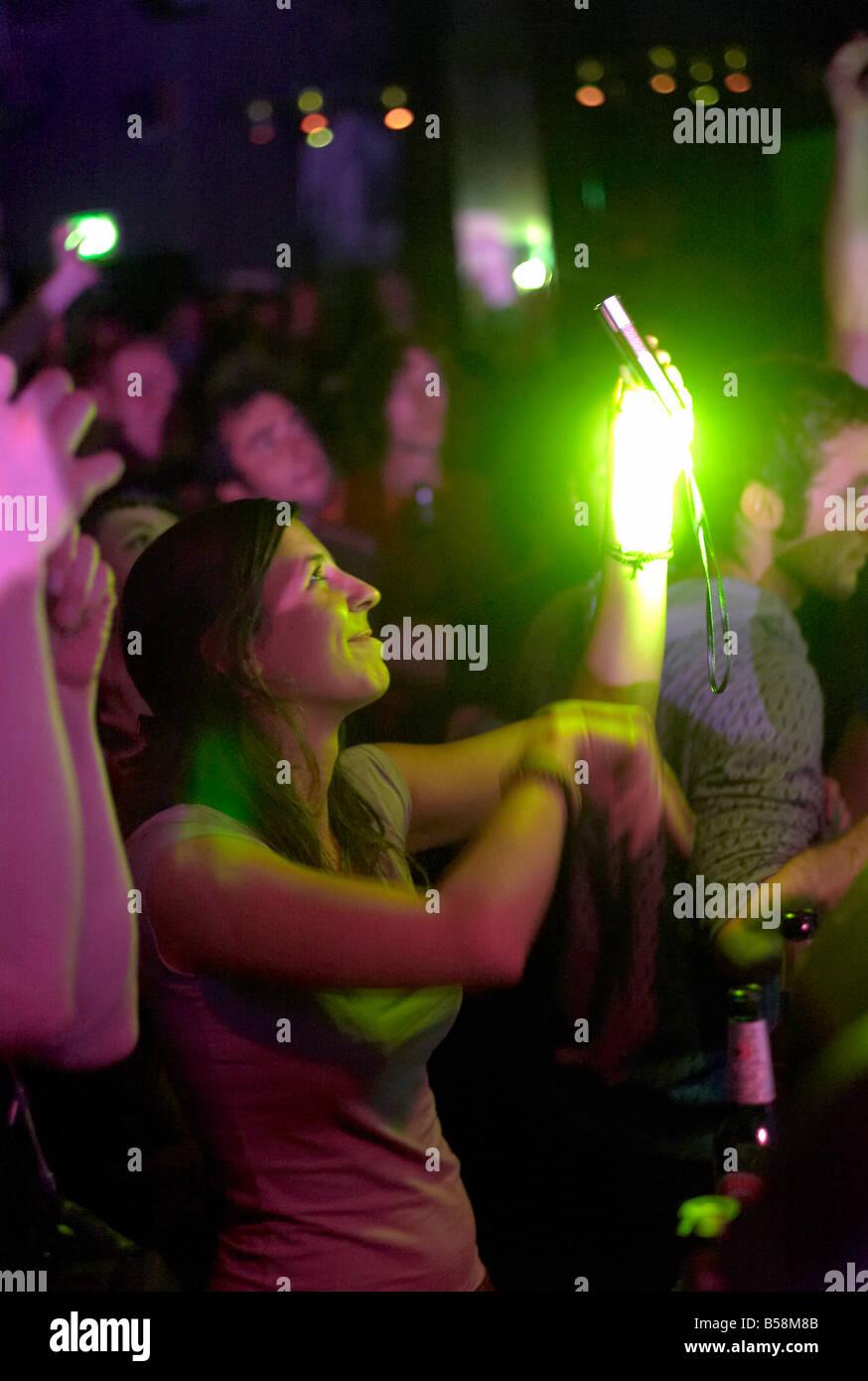 Mädchen bei einem Konzert nimmt ein Foto von einem Darsteller mit ihrem Telefon Stockbild