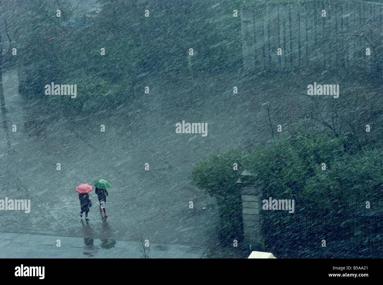 Zwei einsame Figuren mit Regenschirmen gefangen im Sturm, Dublin, Republik Irland, Europa Stockbild