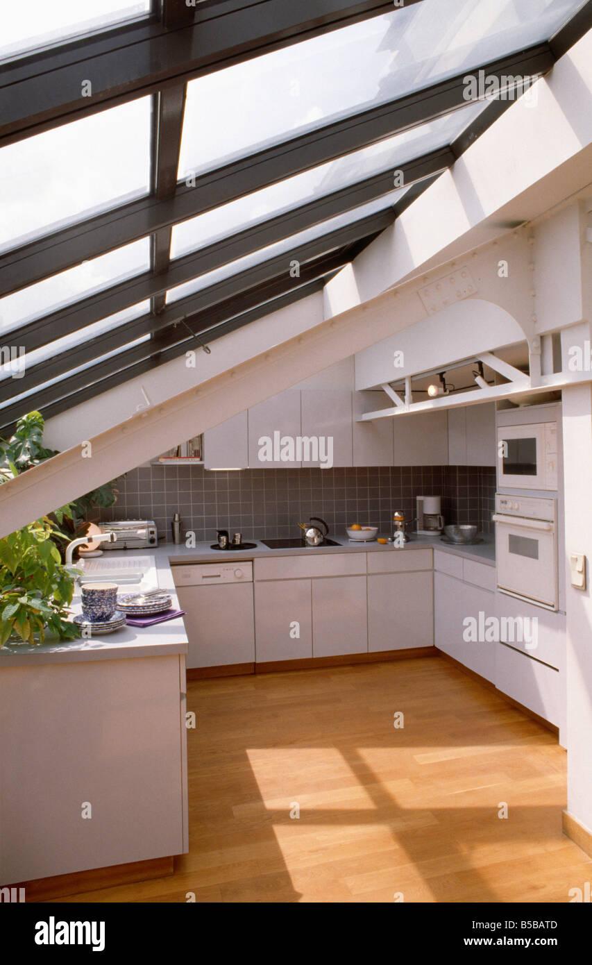 Holzboden In Kompakte Weiße Moderne Loft Küche Mit Wand Doppel Backofen Und  Schräge Glasdach