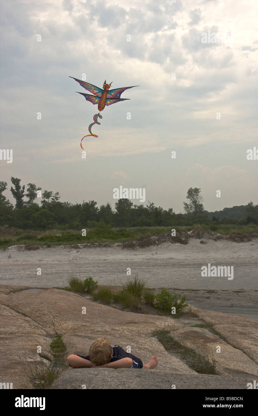 Ein Junge schaut zu einem Drachen fliegen in den Himmel über ihm. Stockbild