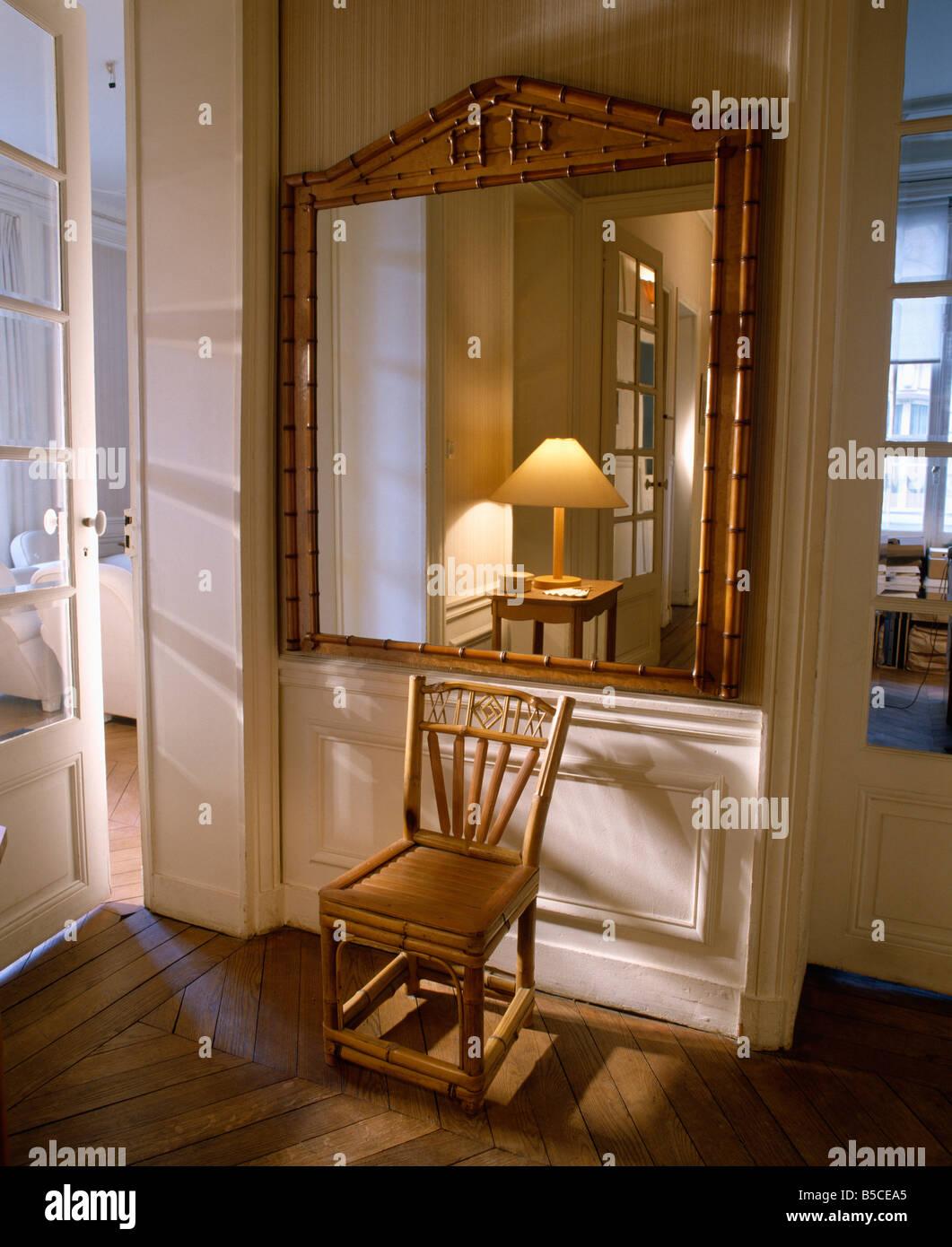 antike bambus stuhl unter großen bambus-gerahmte spiegel in creme