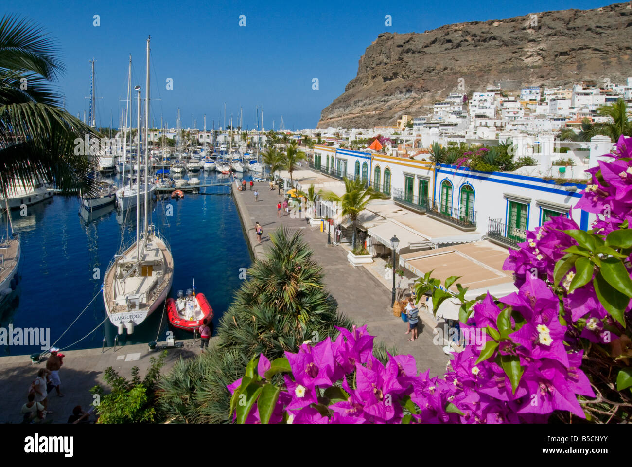 Puerto de Mogan Blick über Bougainvillea Blumen, zu Restaurants, Yachthafen und Promenade. Gran Kanaren Canaria Stockbild