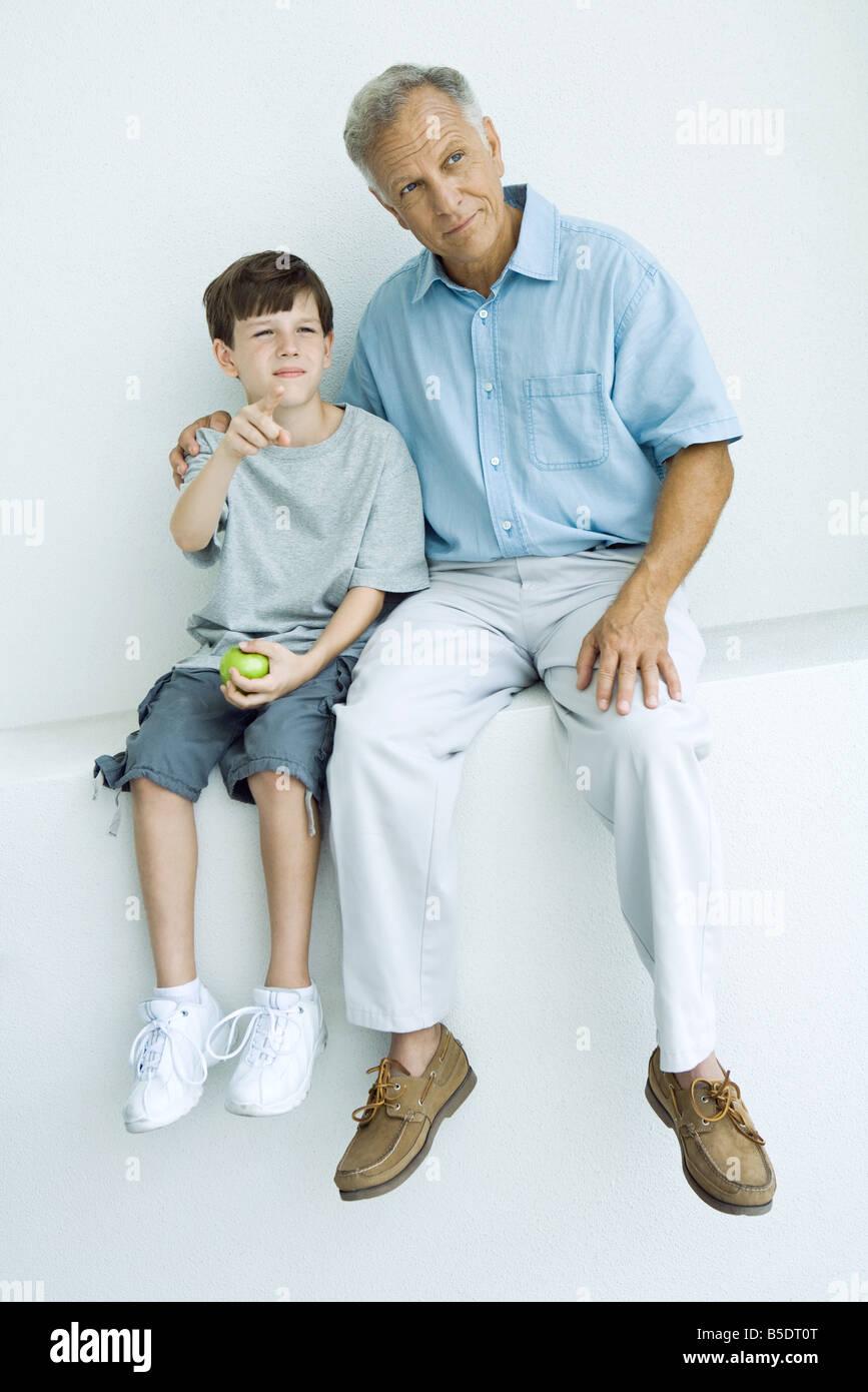 Großvater und Enkel sitzen zusammen auf Felsvorsprung, wegsehen, junge zeigen Stockbild