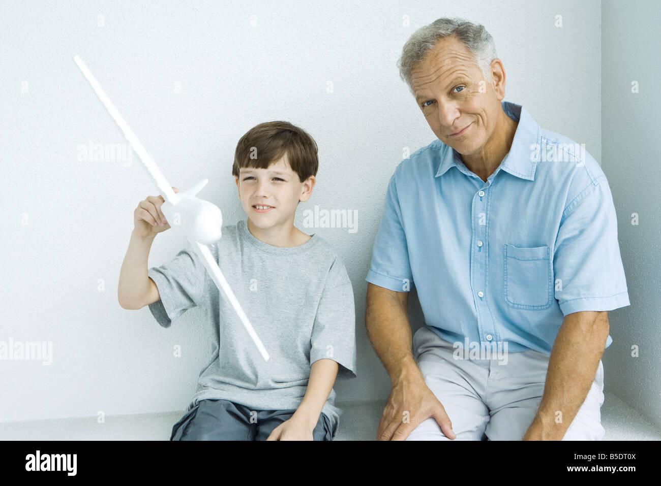 Großvater mit Enkel, lächelnd, als Enkel mit Spielzeugflugzeug spielt sitzen Stockbild