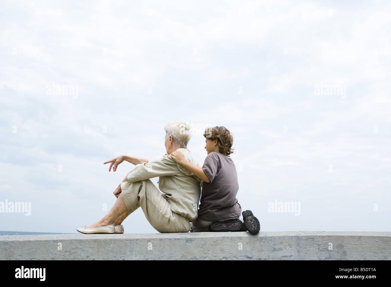 Großmutter und Enkel sitzen zusammen auf Mäuerchen im Freien, betrachten Stockbild