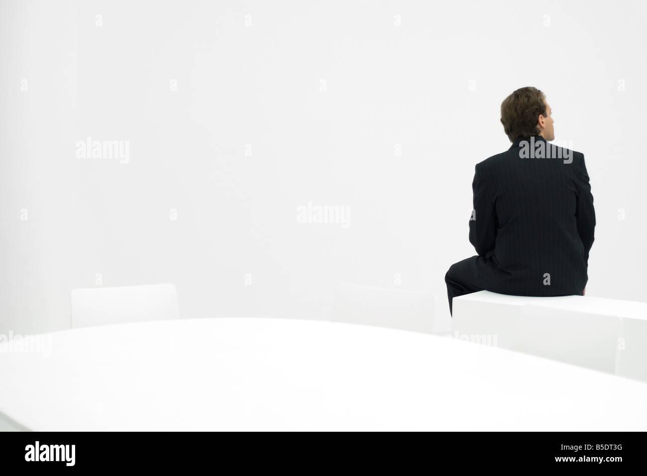 Geschäftsmann, sitzen auf Sims, schauen Weg, Rückansicht Stockbild