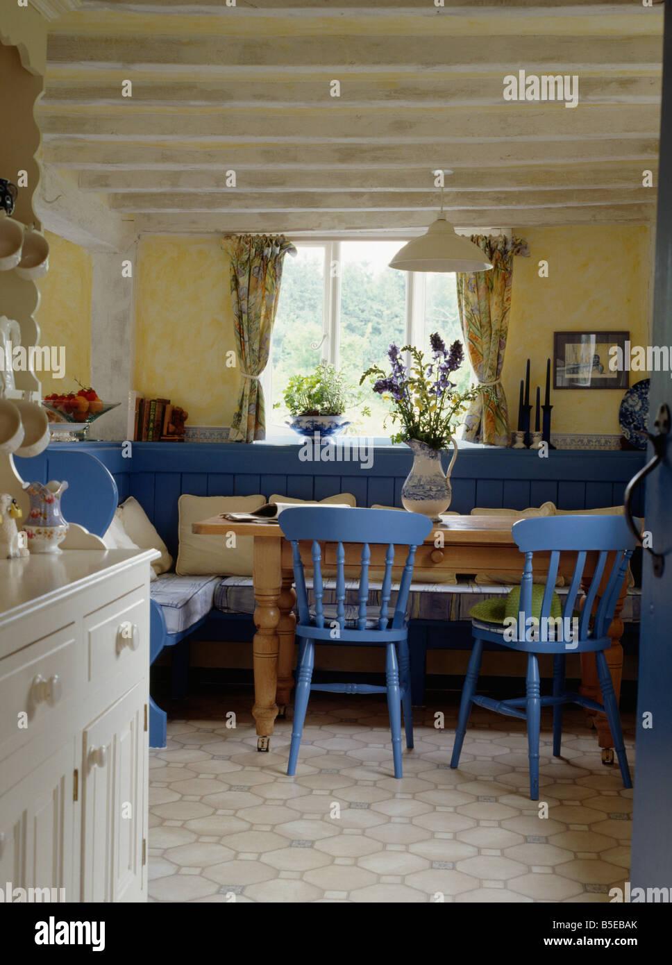 Gemalte blaue Stühle und siedelt sich in gelben Häuschen Küche ...