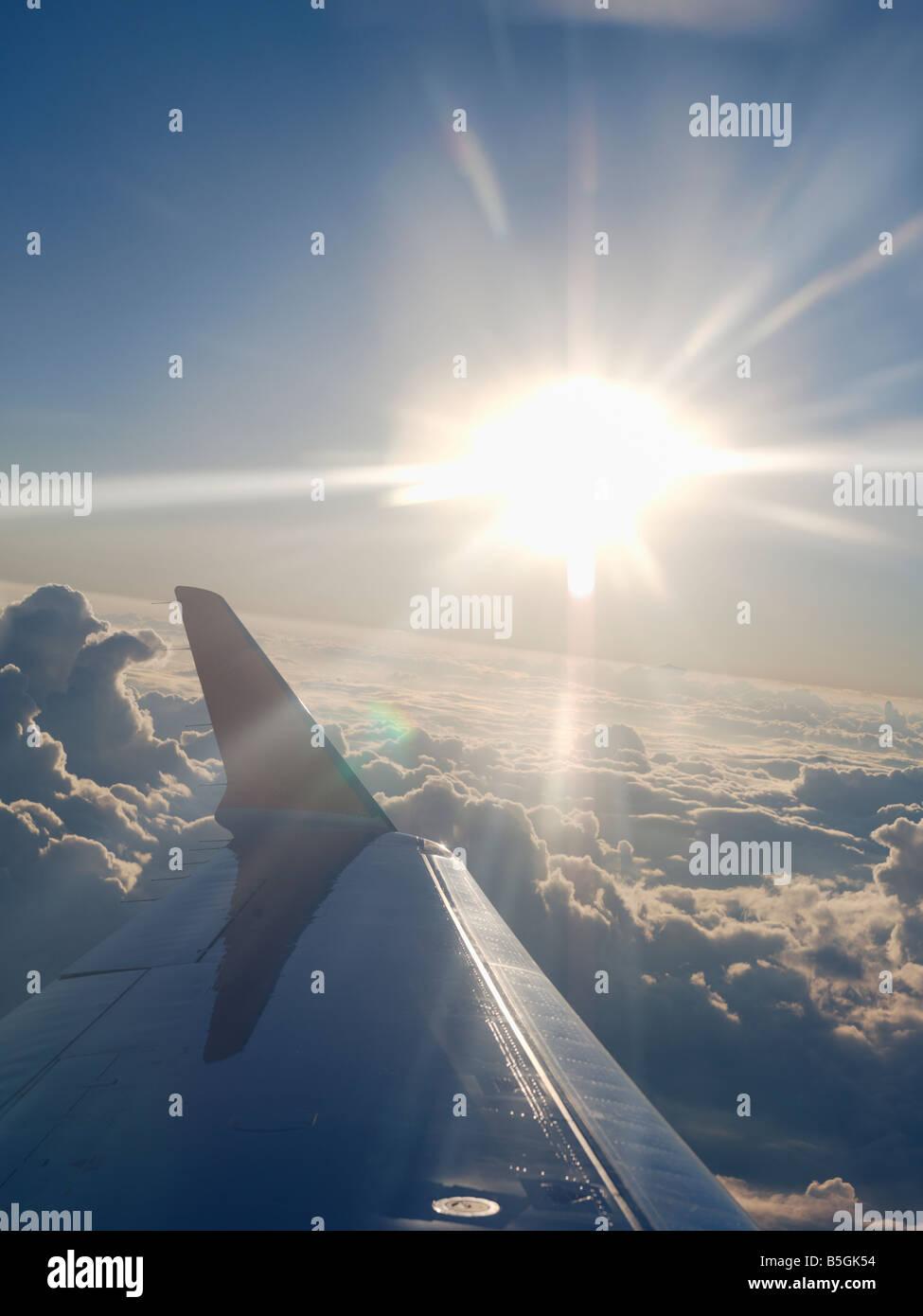 USA, Texas, Houston, Flugzeugflügel und Sonne platzen über Wolken während des Fluges Stockbild