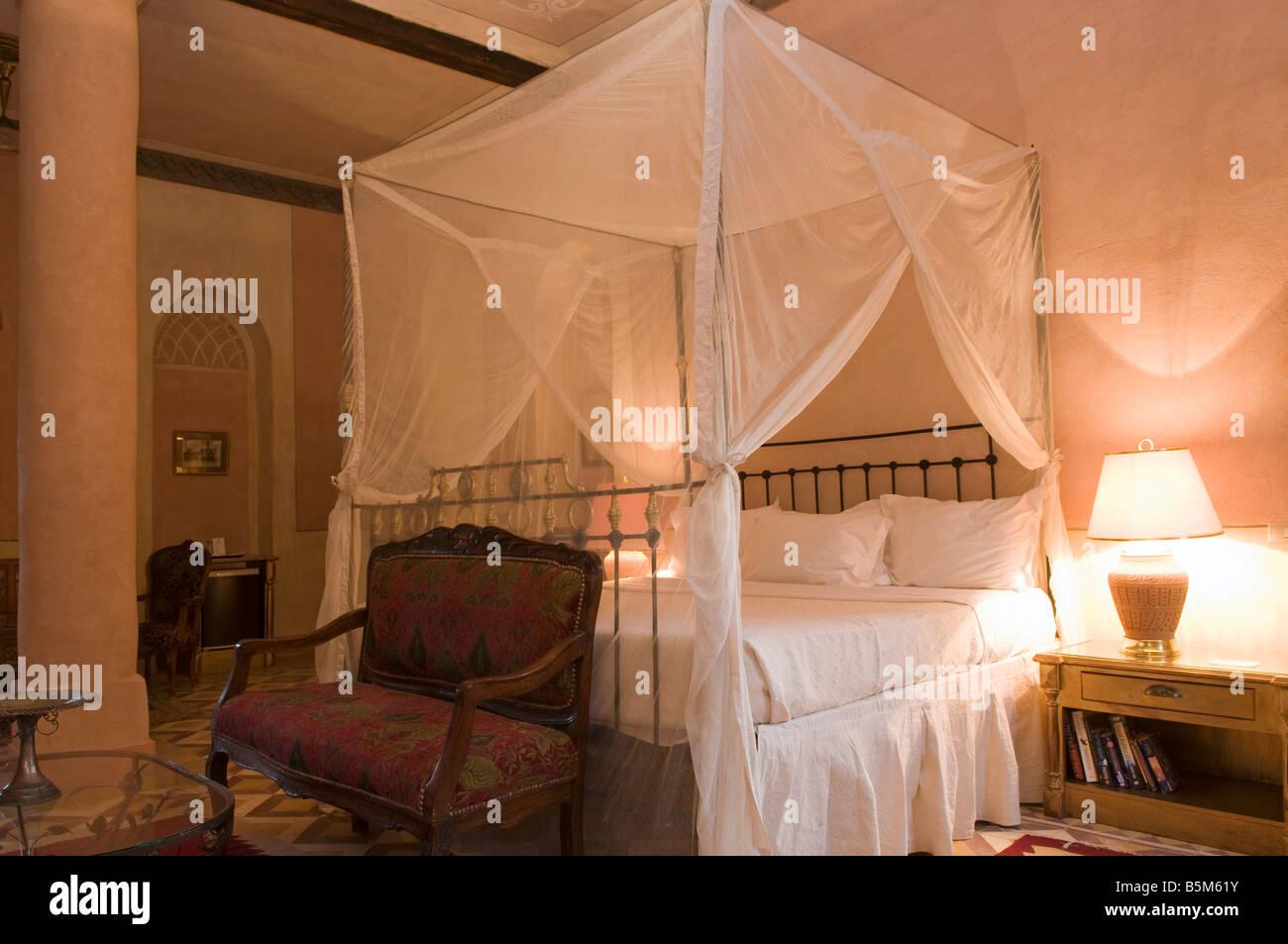 Ein Schlafzimmer mit einem drapiert Moskitonetz im Al Moudira Hotel ...