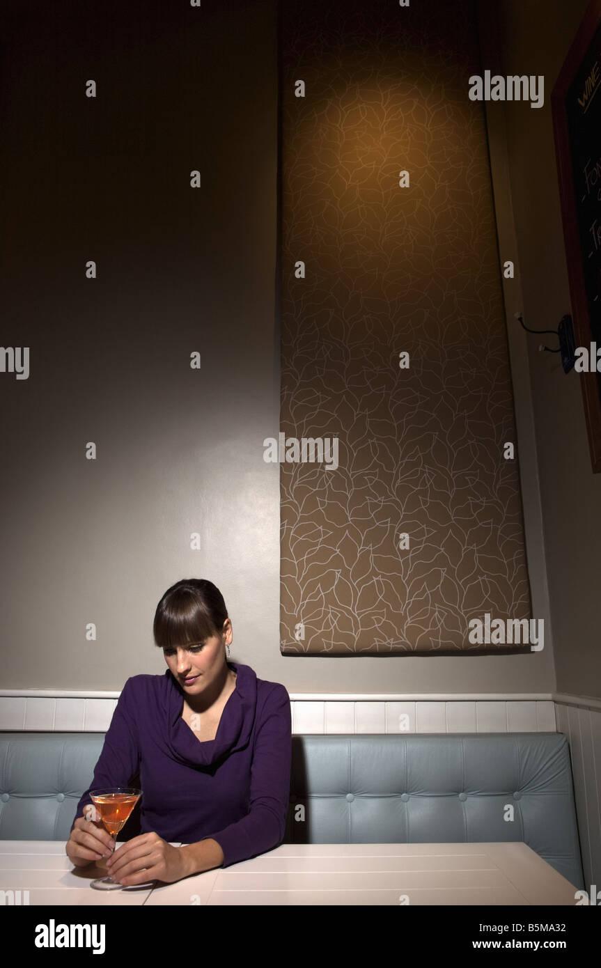 Eine Frau sitzt alleine trinken einen Martini. Stockbild