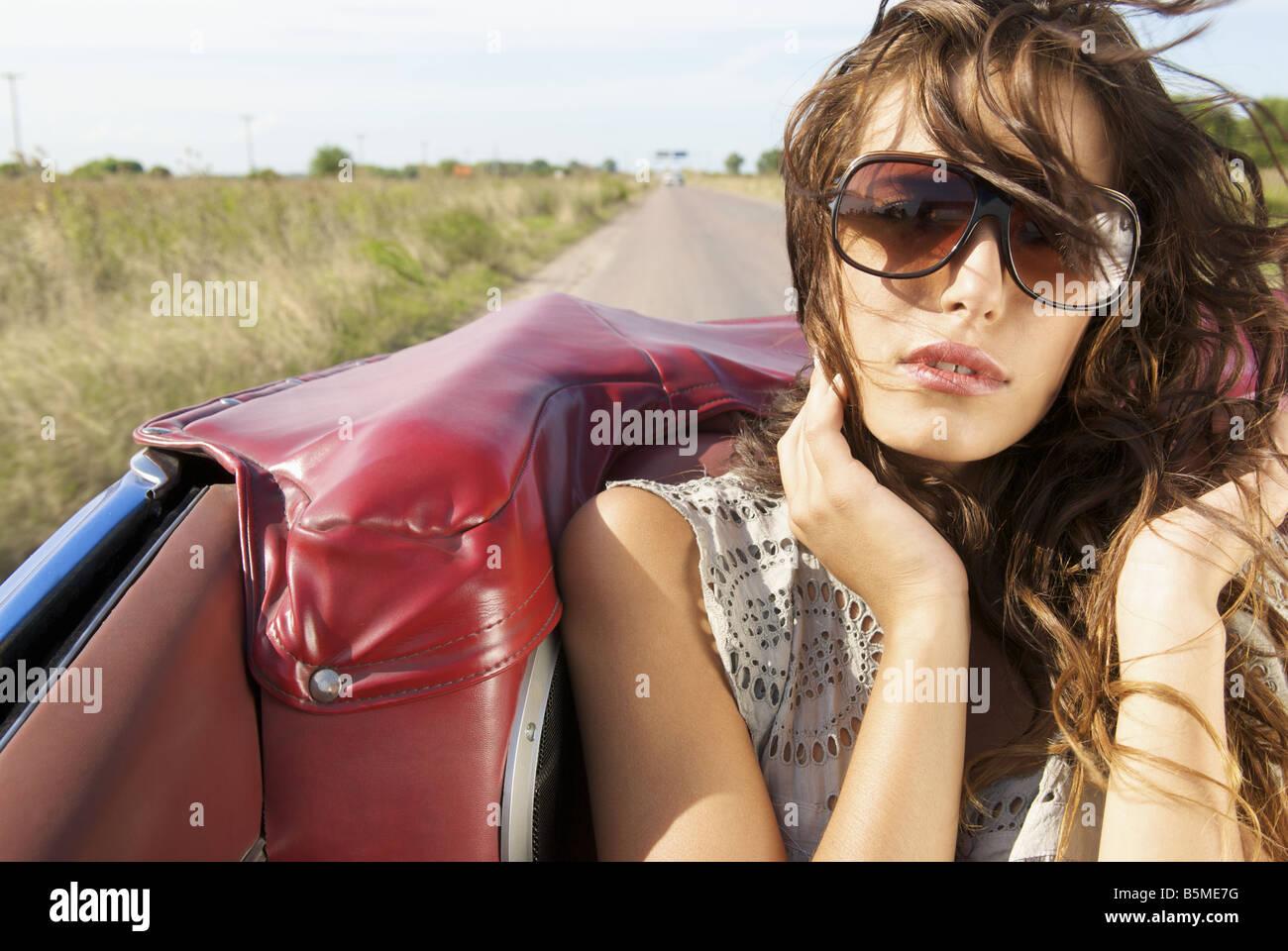 Eine junge Frau sitzt auf dem Rücksitz eines Autos Stockbild