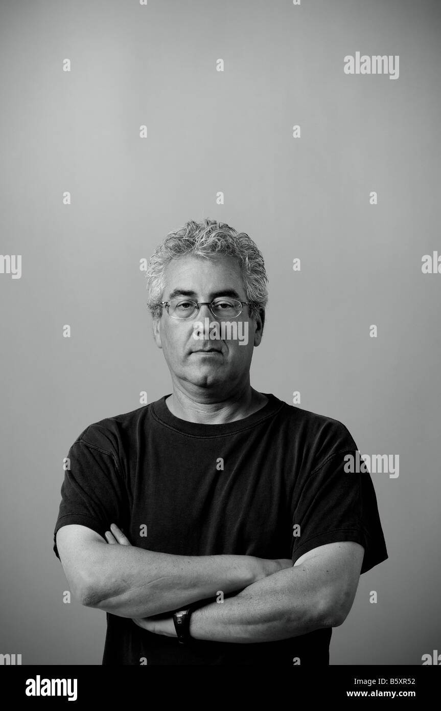 Porträt von ernster Mann mit Armen gefaltet schwarzes T-shirt tragen. Stockbild