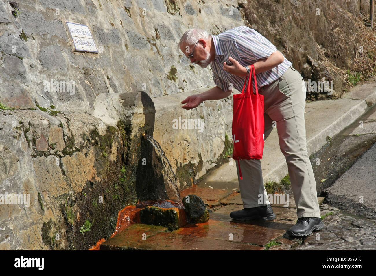Tourist, trinken aus einer Quelle mit natürlich stilles Wasser in Furnas, São Miguel, Azoren, Portugal Stockbild