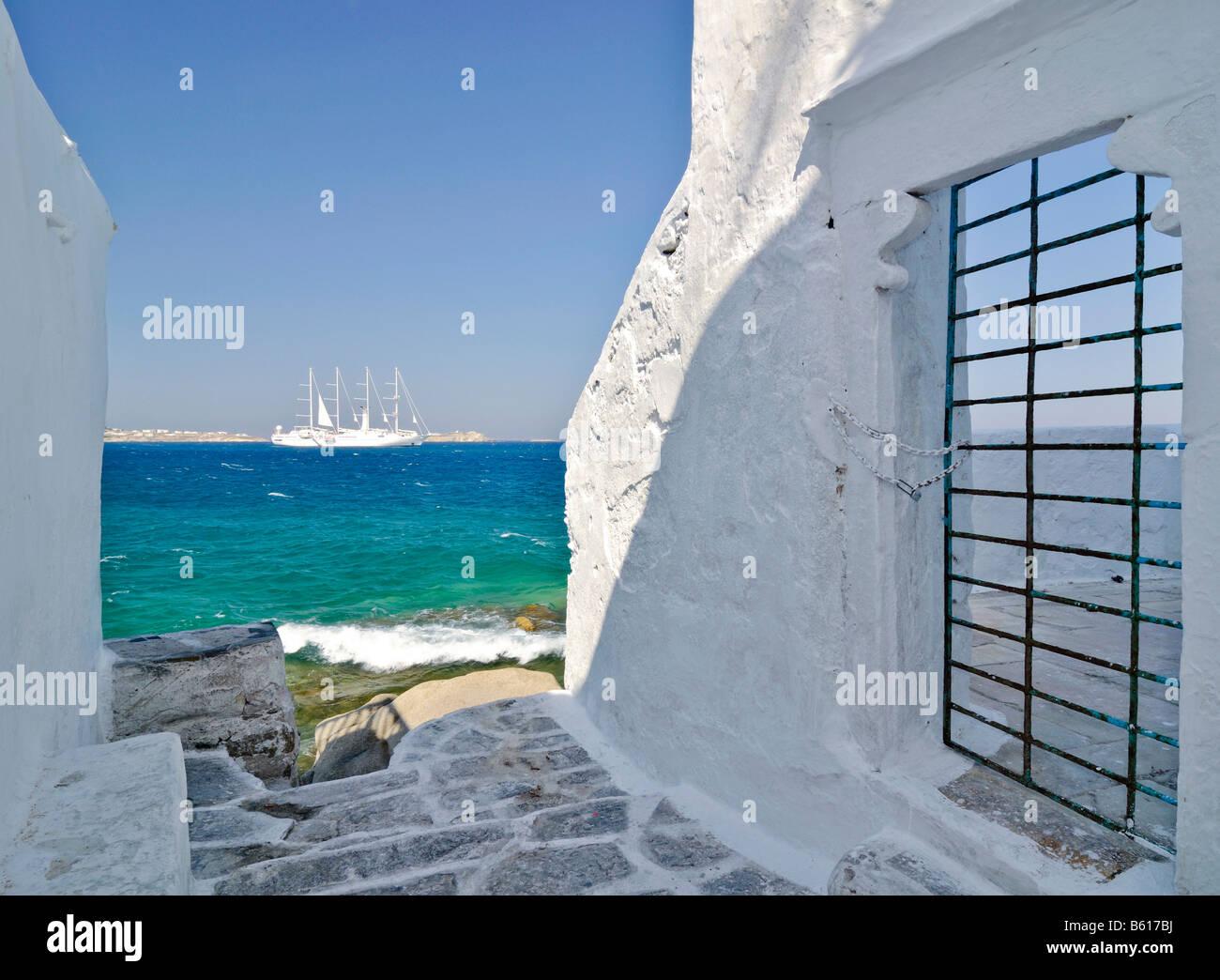 Blick durch eine Gasse mit weißen Wänden und einer Tür mit Bars gegenüber einer vier-Mast-Segelschiff oder der Barke Stockfoto