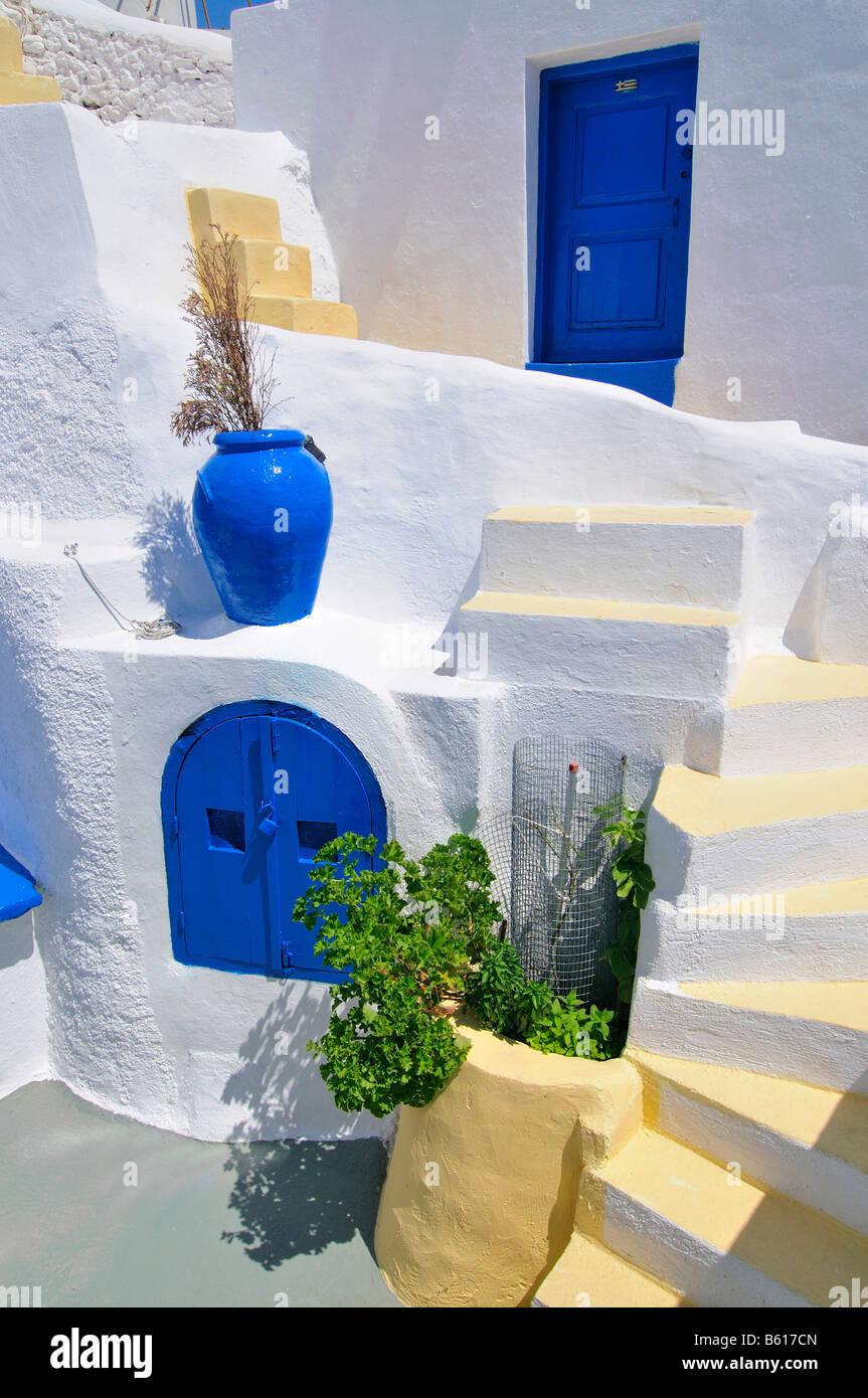 Innenhof mit blauen und gelben Elementen und einer Treppe in einem typisch kykladische Architektur Stil, Oia, Ia, Stockbild