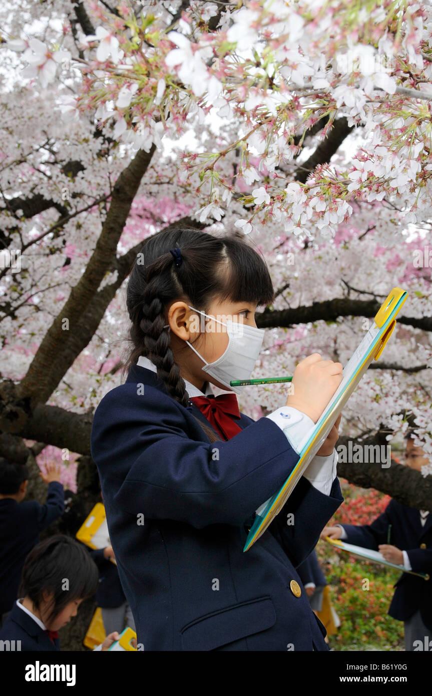 Schulmädchen in Uniform eine Elite Grundschule mit Gesichtsmaske auf ...