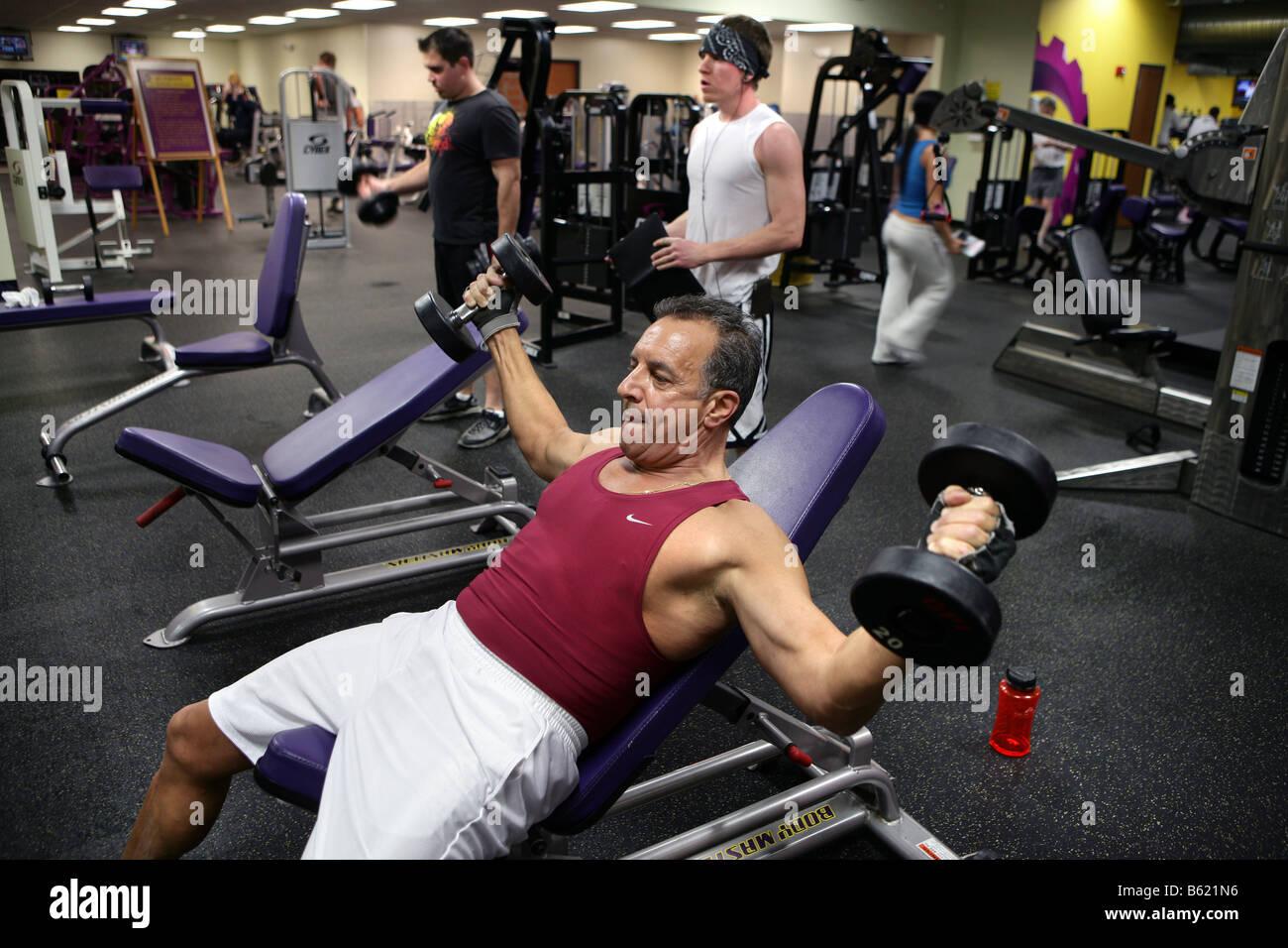 Ein 61 Jahre alter Mann arbeitet in einem Fitnessstudio. Der Mann, der eine Familiengeschichte von Herz-Kreislauferkrankungen Stockbild