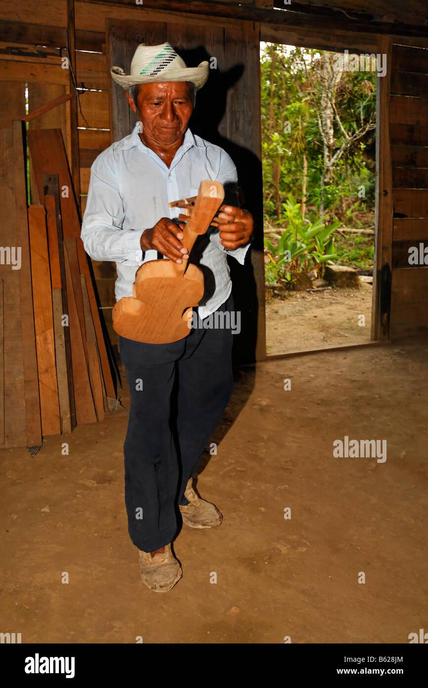 Mann, einheimische Musiker, tuning, eine hausgemachte Instrument, Geige, Holzhütte, Punta Gorda, Belize, Mittelamerika Stockbild