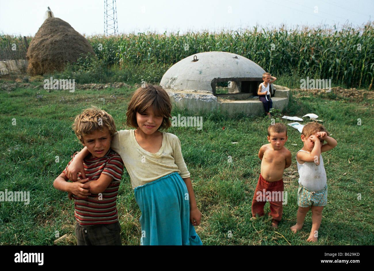 Kinder stehen neben eines der zahlreichen militärischen Verteidigung Pillendosen, die die Landschaft in der Nähe Stockfoto