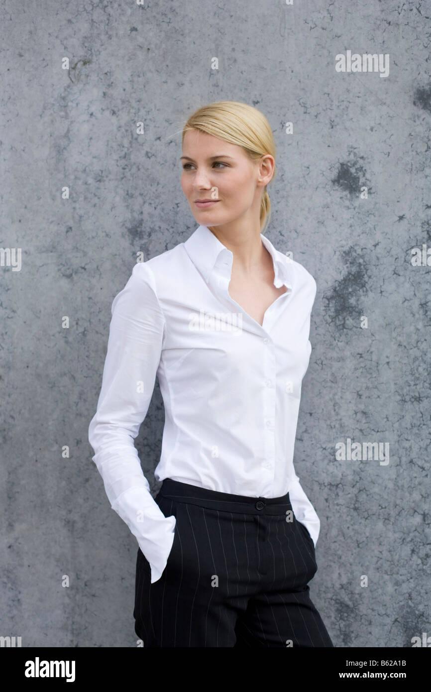 junge blonde frau tr gt business kleidung stehen vor einer grauen wand stockfoto bild 20950087. Black Bedroom Furniture Sets. Home Design Ideas