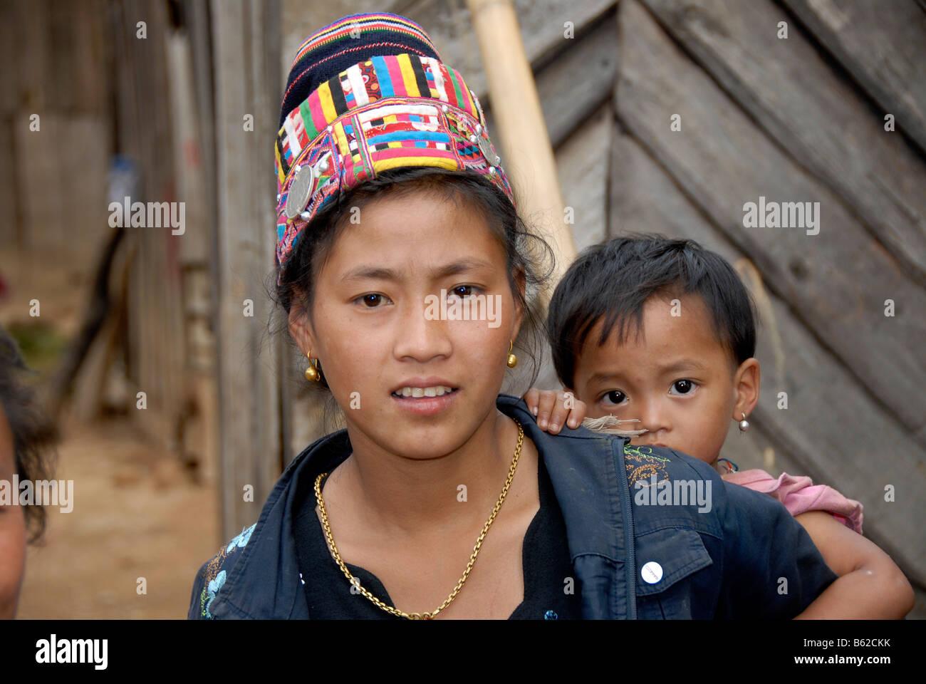 Junge Frau von der ethnischen Gruppe der Akha Lom ein Kind auf dem Rücken tragen und tragen eine traditionelle Stockbild