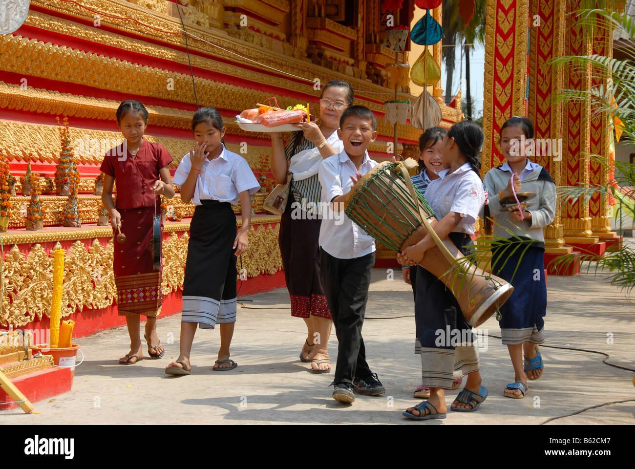 Buddhistischen Familie mit Kindern bei einem fröhlichen Spaziergang rund um den Tempel mit einer Trommel und Stockbild