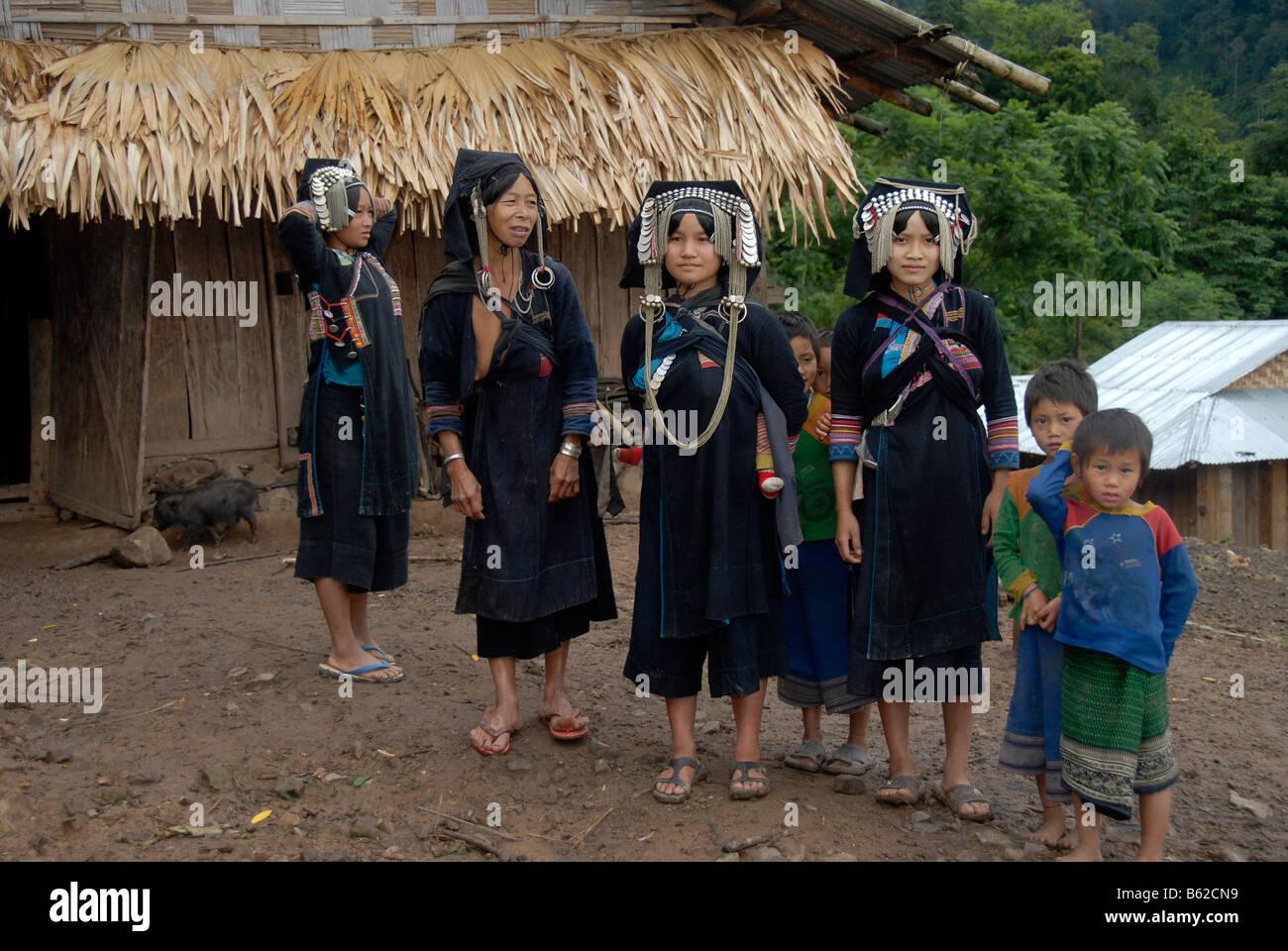 Vier Frauen des Stammes Akha Phixo in traditioneller Tracht mit Kindern, Ban Phapoun Mai, Provinz Phongsali, Laos, Stockbild