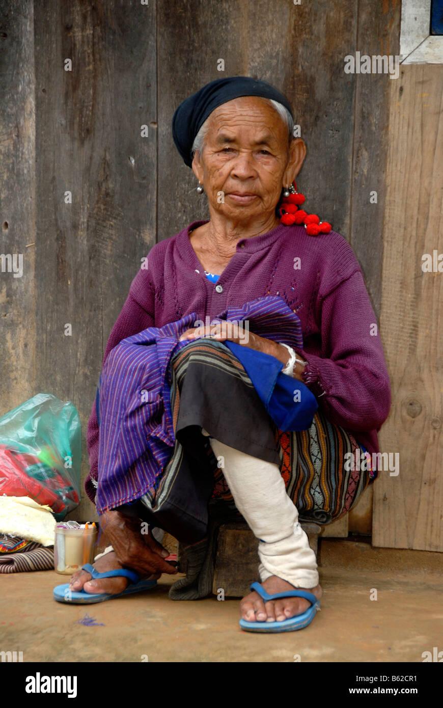 Alte Frau des Stammes Phunoy gekleidet in die typische weiße Leggings und Kopfschmuck mit roten Pompons, Ban Stockbild