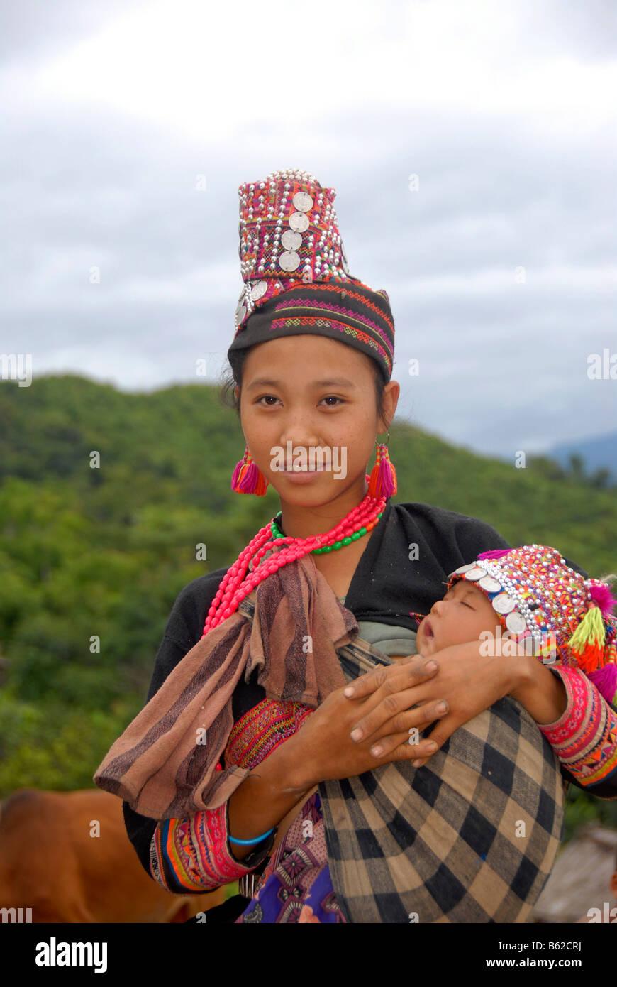 Junge Frau des Stammes Akha Pala in traditioneller Tracht mit ihrem Baby, Ban Pakha, Provinz Phongsali, Laos, Südostasien Stockbild