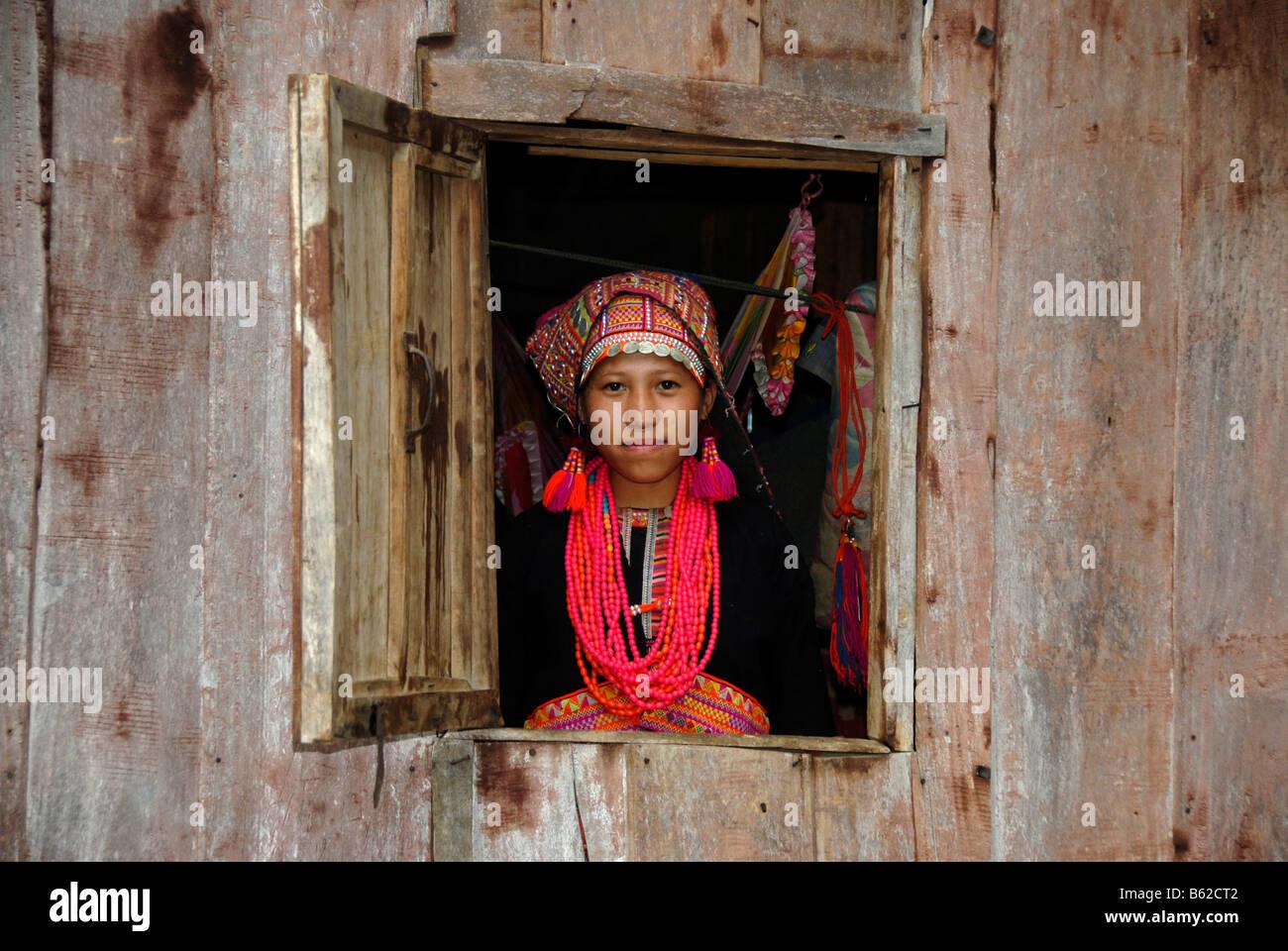Junge Frau des Stammes Akha Pala Blick aus einem Fenster gekleidet in einem bunten Kopf-Kleid und eine rote Halskette, Stockbild