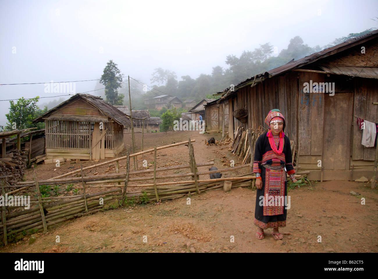 Junge Frau des Stammes Akha Pala tragen bunte Tracht stehen im Dorf Ban Saenkham Tai, Phongsali P Stockbild
