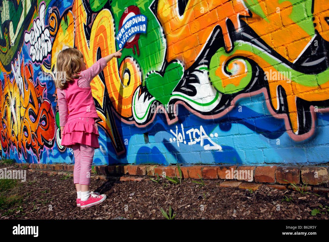 Mädchen stehen und deutete auf eine Graffiti-Wand-Wallart im Rahmen ...