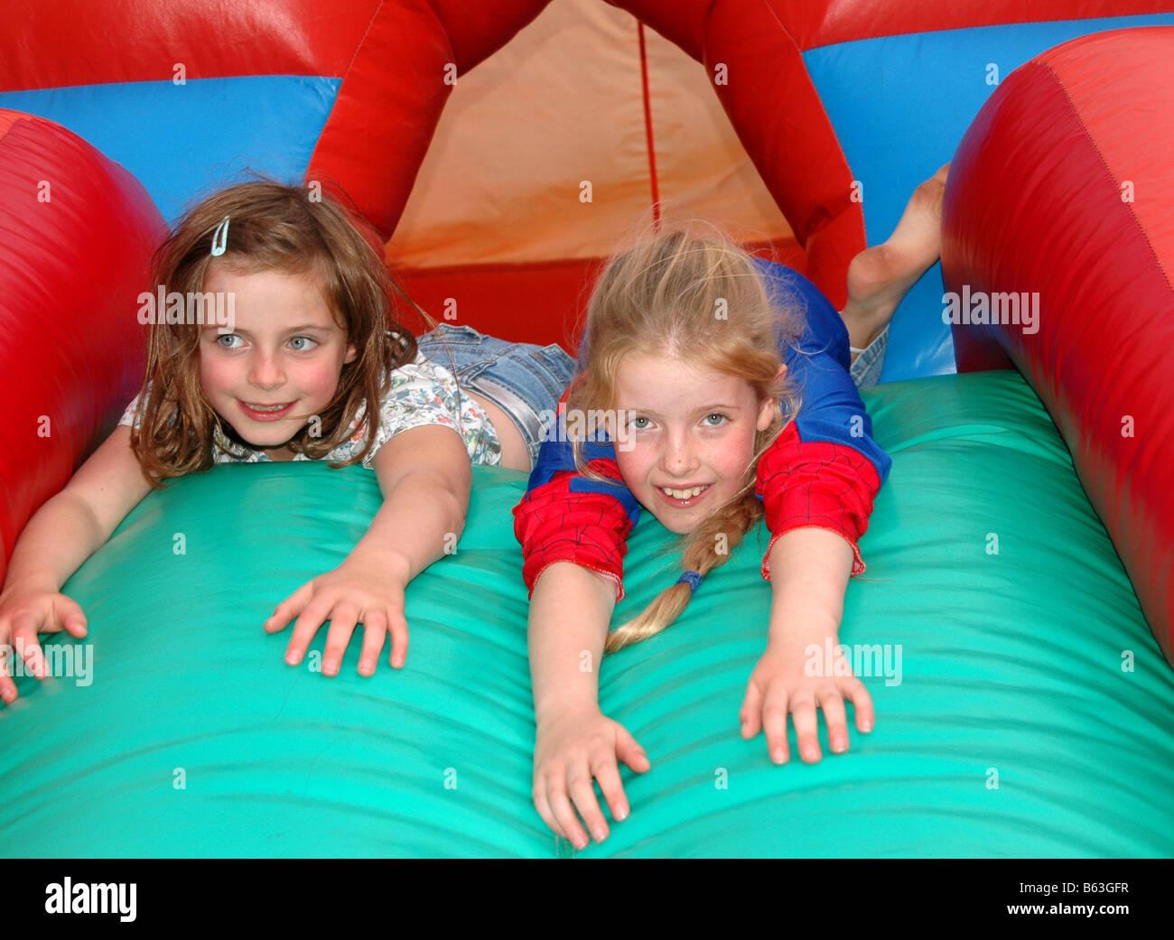 Zwei junge Mädchen spielen in der Hüpfburg. Stockbild