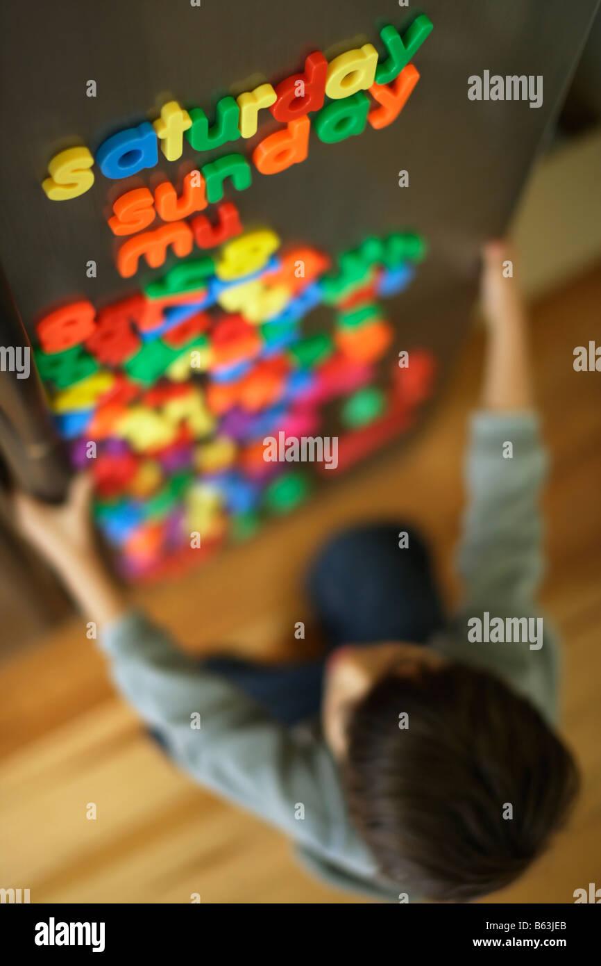 Sechs Jahre alter Junge Zauber Tage mit Kühlschrank-Magnete Stockbild