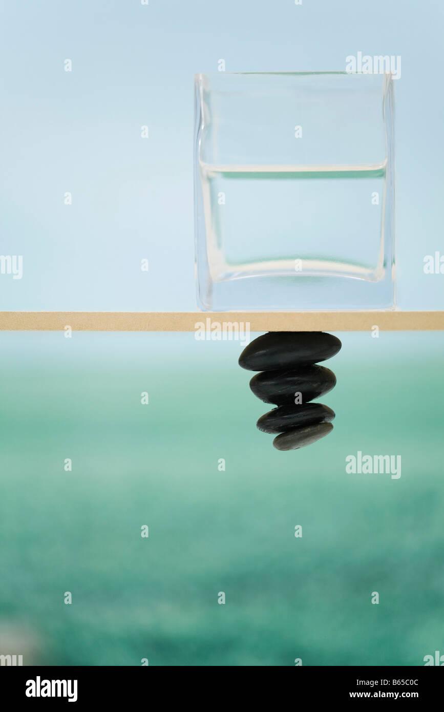 Glasbehälter mit Wasser sitzen auf Sims, Steinhaufen, die unter Schwerkraft trotzend gefüllt Stockbild
