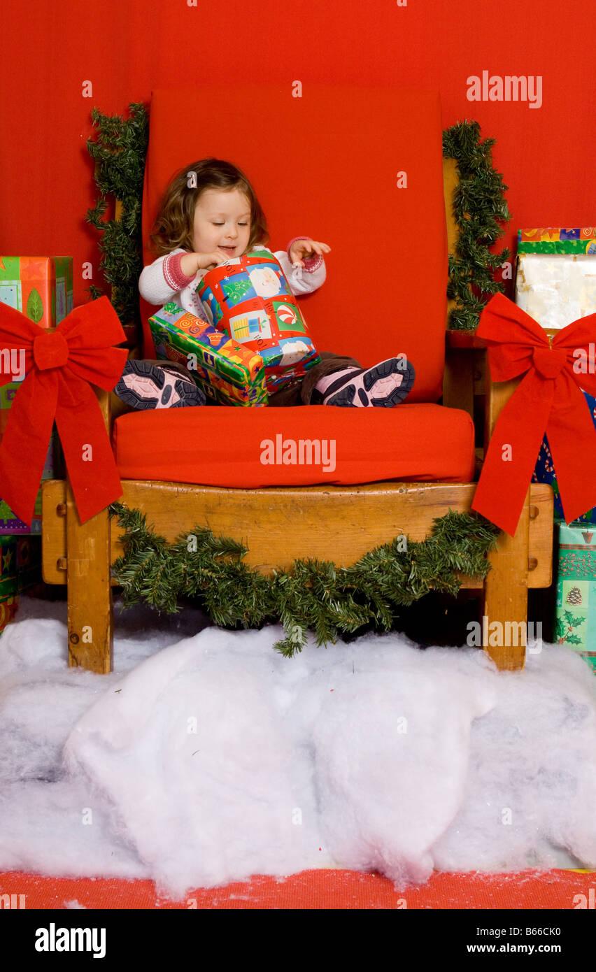 2 Jahre altes Mädchen ihr Weihnachtsgeschenk auf Santas Thron ...