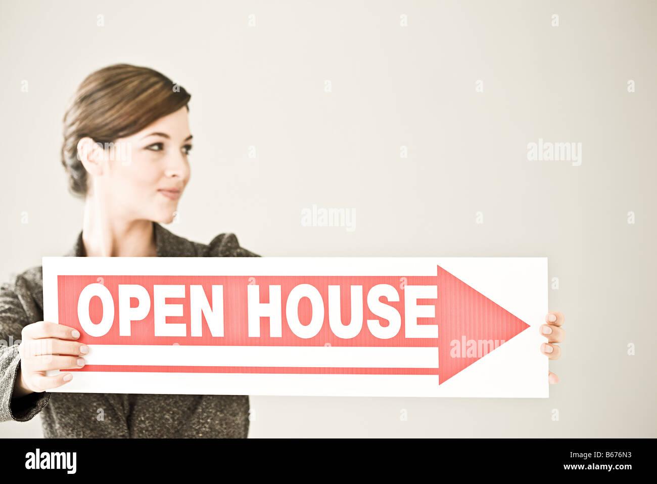 Eine Frau mit einem Tag der offenen Tür-Schild Stockfoto