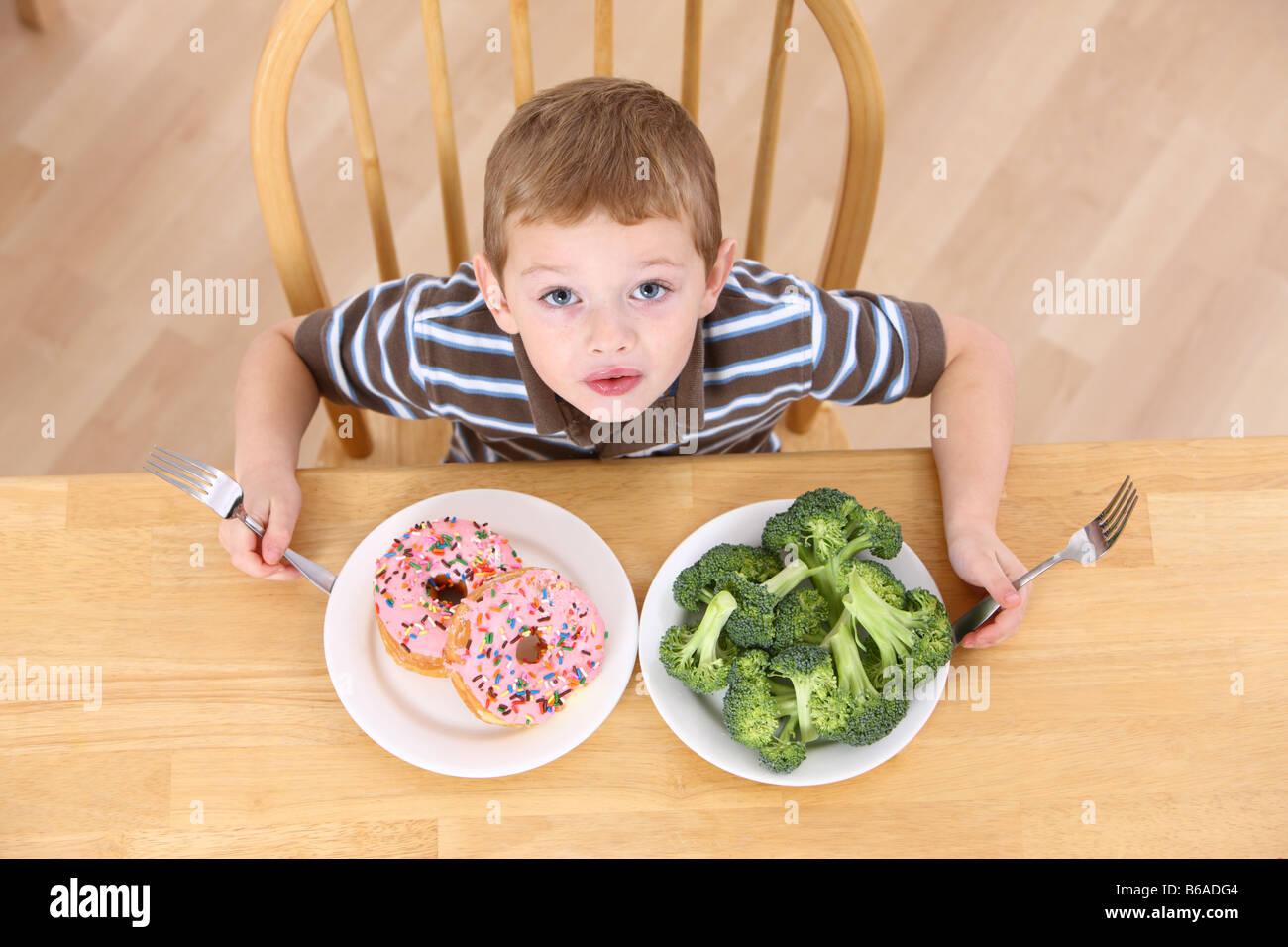 Junge mit Platten von Broccoli und Krapfen Stockbild