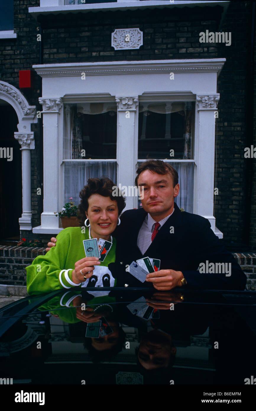Ein neunziger Jahre paar Stellen außerhalb ihrer Clapham Reihenhaus mit Kredit Karten symbolisiert den Kreditboom Stockbild